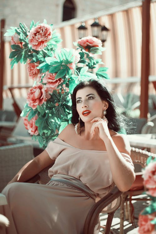 Charming woman in elegant dress sitting on chair on terrace in town in sunny day and looking away