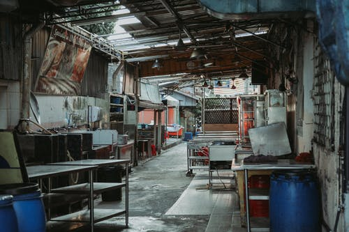 Interior of abandoned cafeteria with tables shelves and banner and lamps hanging on destroyed roof located on street of town