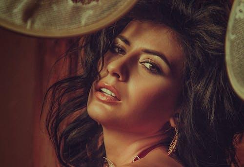 Charming woman with long dark hair looking at camera