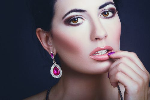 Charming female with bright makeup in stylish accessories touching lips and looking at camera against dark background