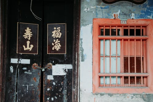 Old shabby door with written hieroglyphs and red window with metal grid on wall of aged building on street in city