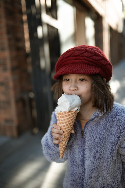 Woman in Blue Coat Holding Ice Cream Cone