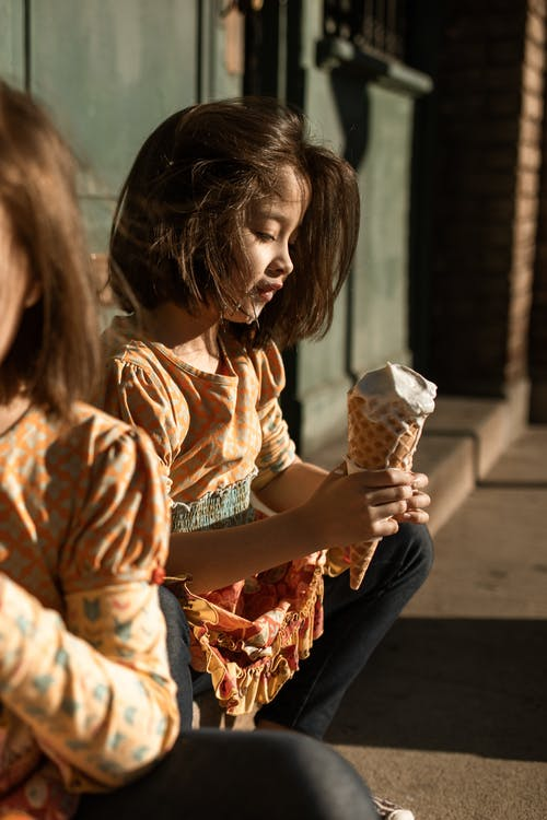 Woman in Brown and White Floral Dress Holding Ice Cream Cone