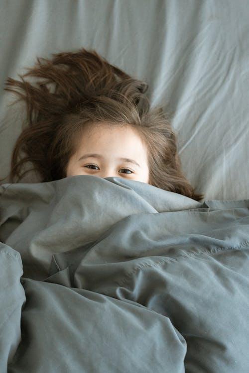 Fille Couchée Sur Le Lit Recouvert D'une Couverture Bleue