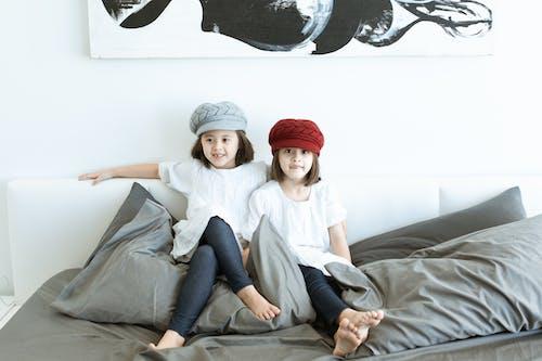 2 Femmes Assises Sur Un Lit Noir Et Blanc