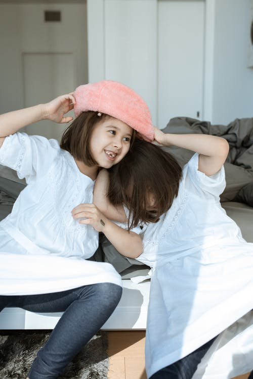 Femme En Chemise Blanche Et Chapeau Rose Assis Sur Un Tableau Blanc