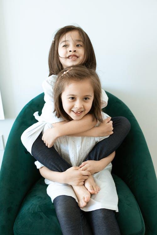 躺在绿色的沙发上的白色长袖衬衫的微笑女孩
