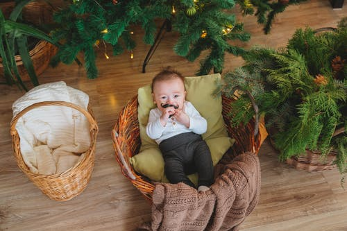 From above of adorable little boy lying on pillow and blanket in basket near Christmas decorations and looking at camera