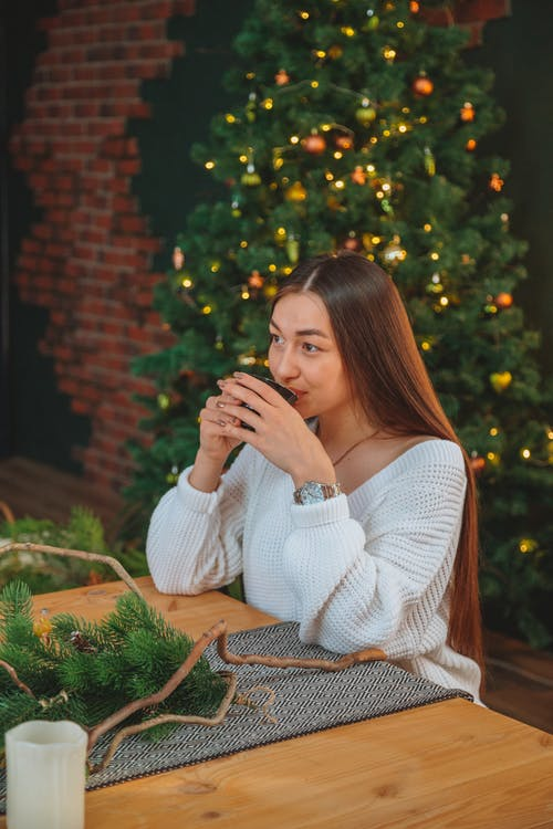 Dreamy woman drinking tea against Christmas tree
