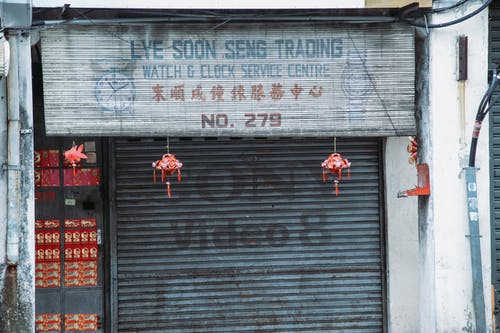 Exterior of closed aged service with signboard and traditional hanging decorations and black rolling gates located on street in city