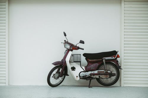 Motorcycle parked near white wall