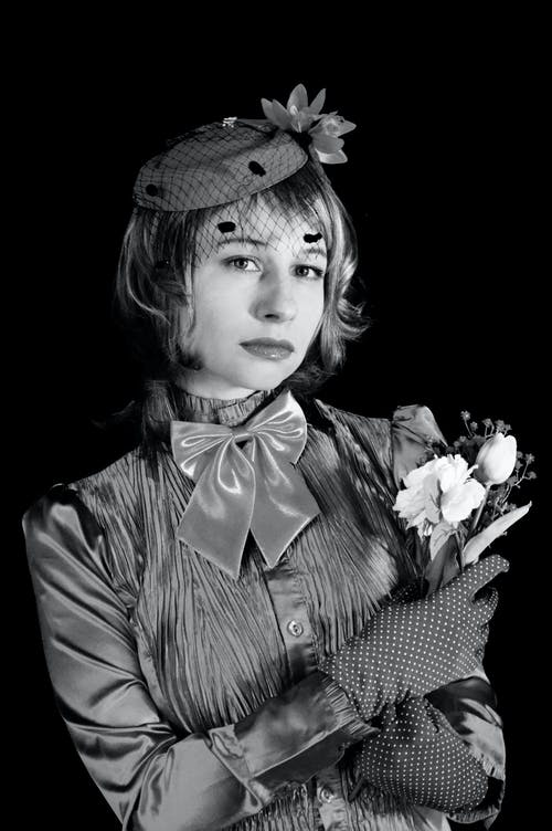 Serious young lady in retro outfit against black background