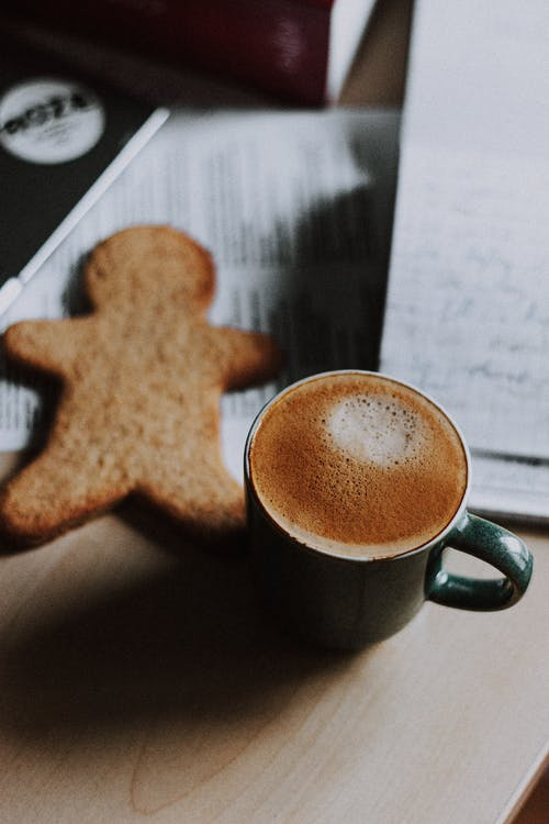Cup of delicious cappuccino and cookie on workplace