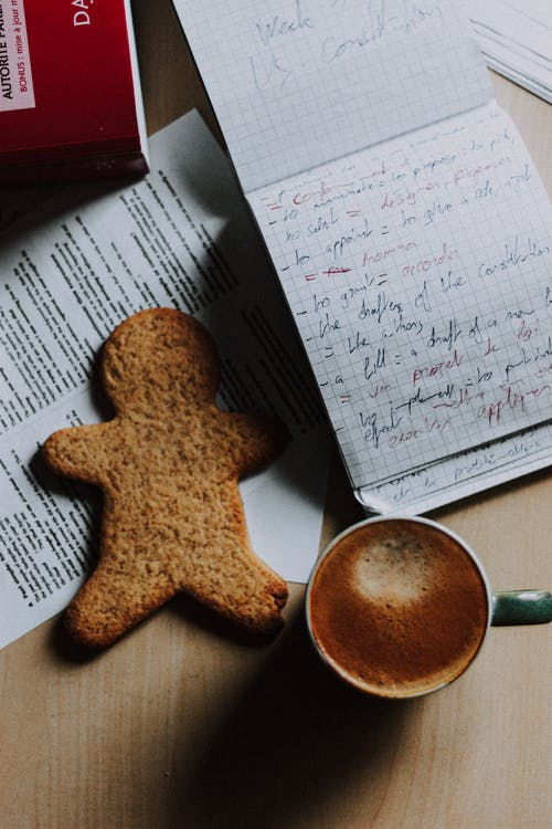 Cup of cappuccino and cookie placed on desk near notepad
