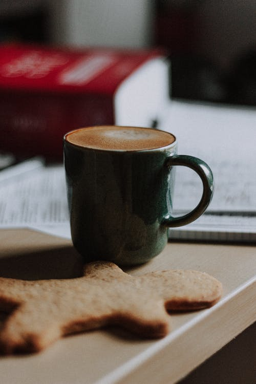 Aromatic tasty cappuccino and delicious gingerbread cookie placed on desk near papers and books in home office