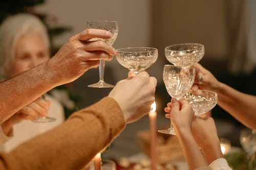 Person Holding Clear Wine Glasses