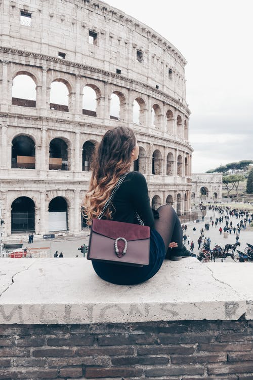 Woman with stylish bag resting on stone wall near Colosseum