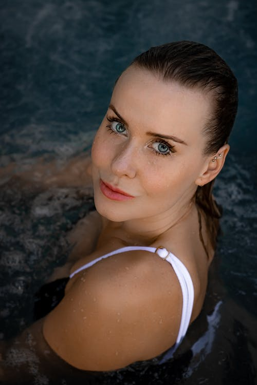 From above of calm female with wet hair looking at camera while resting in swimming pool