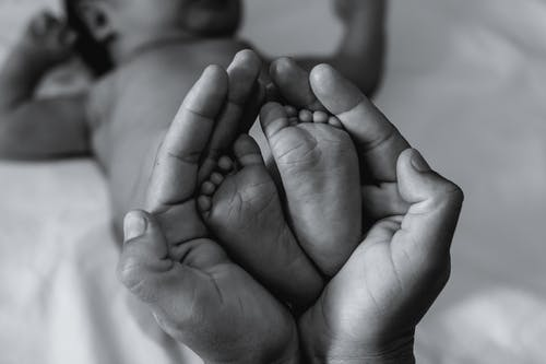 From above of black and white crop anonymous parent holding adorable newborn baby feet lying on bed