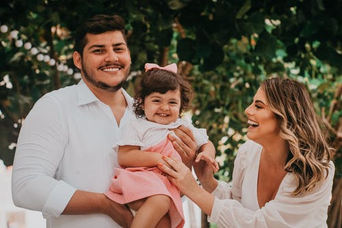 Joyful young ethnic parents in stylish clothes laughing while hugging cute little daughter during family event in green garden