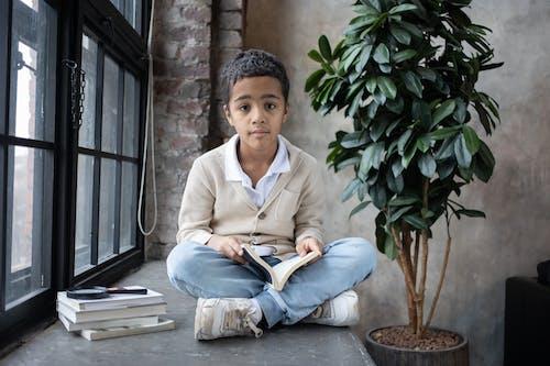 Adorable Arabian boy sitting on windowsill with opened book on knees