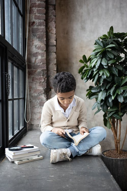 Full body of focused little Arabian boy wearing casual clothes sitting on wide windowsill with magnifier and copybooks while reading interesting book