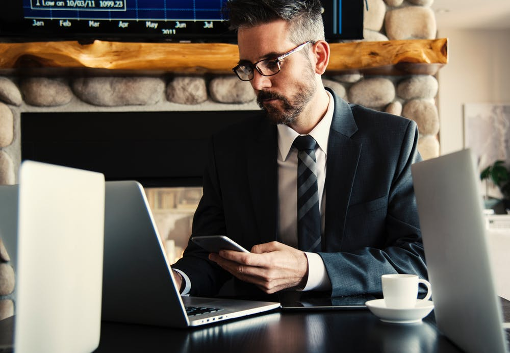 Dark-haired lawyer working with a computer at his desktop in the office.   Photo: Pexels
