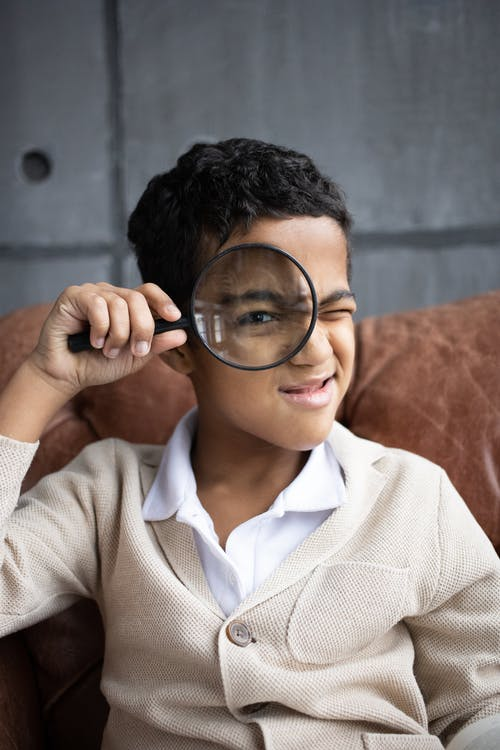 Curious Arabian schoolboy wearing white shirt with cardigan sitting on comfortable couch and looking through magnifying glass at camera indoors