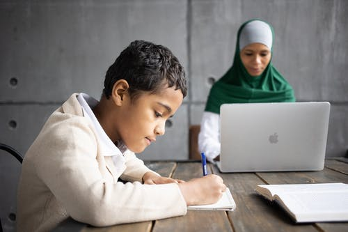 Serious Arabian boy writing homework while sitting at table with mother wearing traditional hijab working remotely on portable laptop