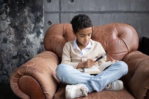 坐在橙色沙發上的白色禮服襯衫和藍色牛仔牛仔褲的男人