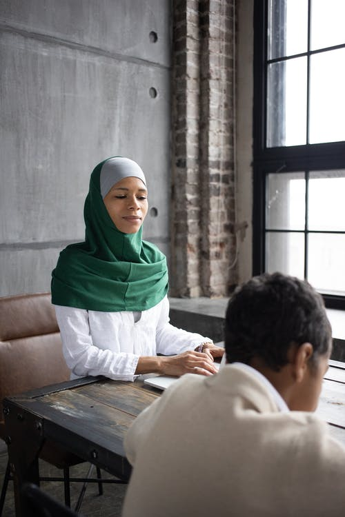Concentrated Arabian female wearing green hijab sitting at table with laptop near son preparing project for school in modern apartment