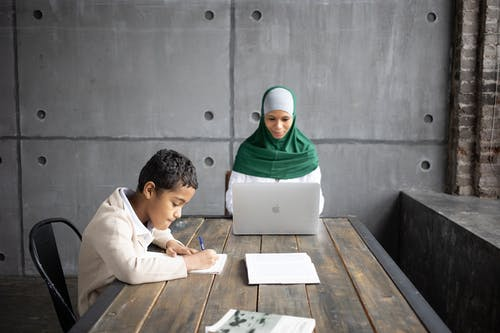 Positive Arabian mother using modern laptop while sitting together with son