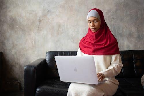 Mujer En Rojo Hijab Sentada En Un Sofá De Cuero Negro