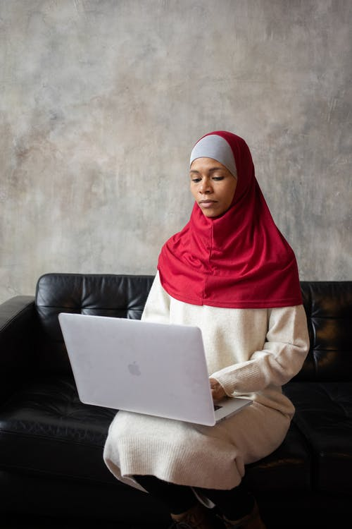 Thoughtful Arabian female freelancer working remotely on portable netbook