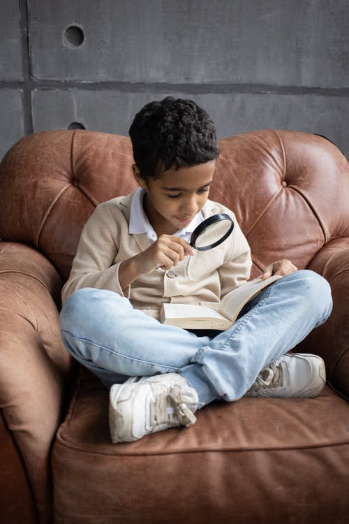 Full body of adorable little Arabian boy wearing jeans and sneakers sitting in leather armchair with interesting book and reading through magnifier