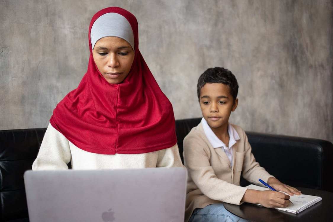 Muslim pensive ethnic mother typing on netbook while son with pen taking notes in notebook