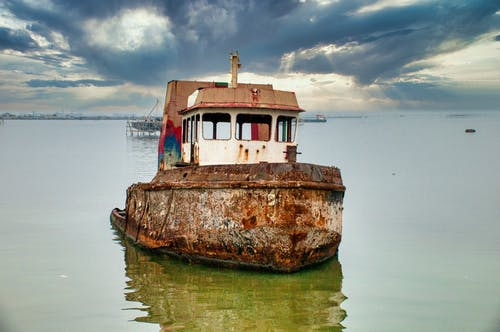 Old rusty abandoned ship moored in calm water of ocean under cloudy sky in daytime