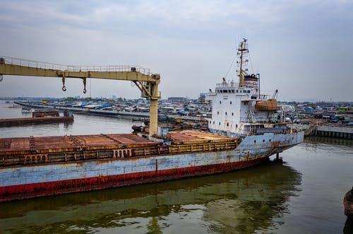Aged cargo vessel moored in port in calm water under cloudy sky in daytime