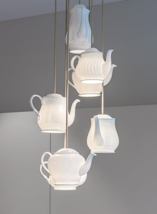 Interior of room with small white lamps in shape of pot hanging from ceiling near wall