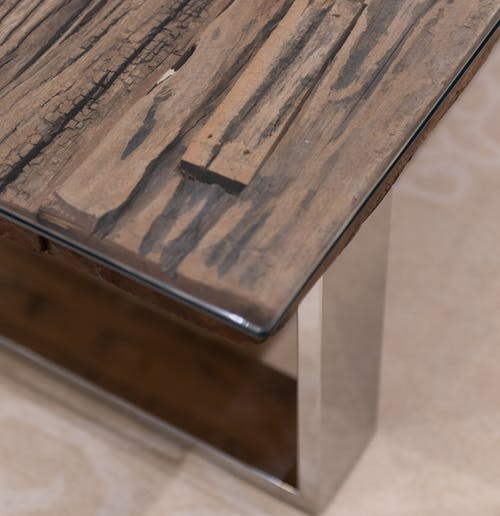 High angle of wooden brown table with metal details placed on floor in light room