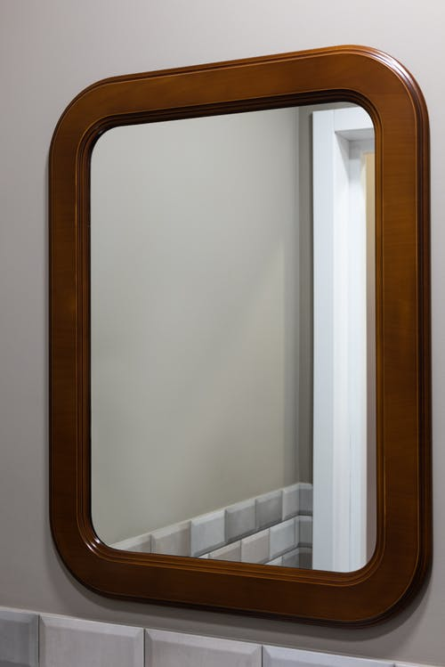 Interior of modern light bathroom with mirror placed on gray wall near door