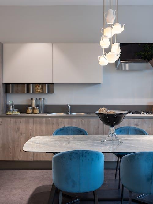 Kahverengi Ahşap Masa Yanında Mavi Plastik Sandalye