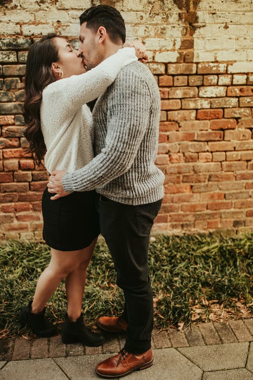 Full length side view of young couple in casual clothes standing in street in summer day near brick wall on sidewalk near grass and kissing gently while hugging