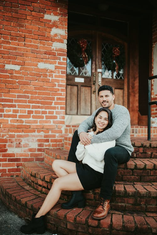 Couple sitting on stairs and hugging near building
