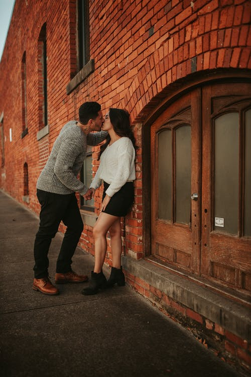 Anonymous couple kissing in street near building