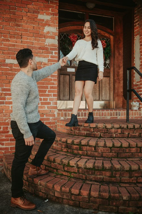 Carefree young couple standing on brick doorsteps