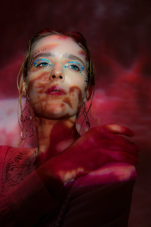 Dreamy young female with eyeshadows and glowing lipstick looking away in colorful studio with pink light with shadows on face and hand on shoulder