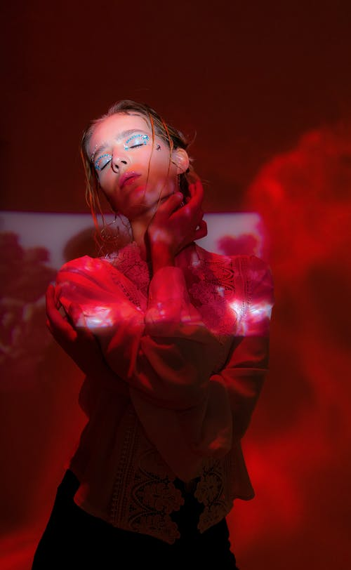 Pensive young female with glowing blue eyeshadows in dark studio covered with red shades and lights with hand on neck and closed eyes