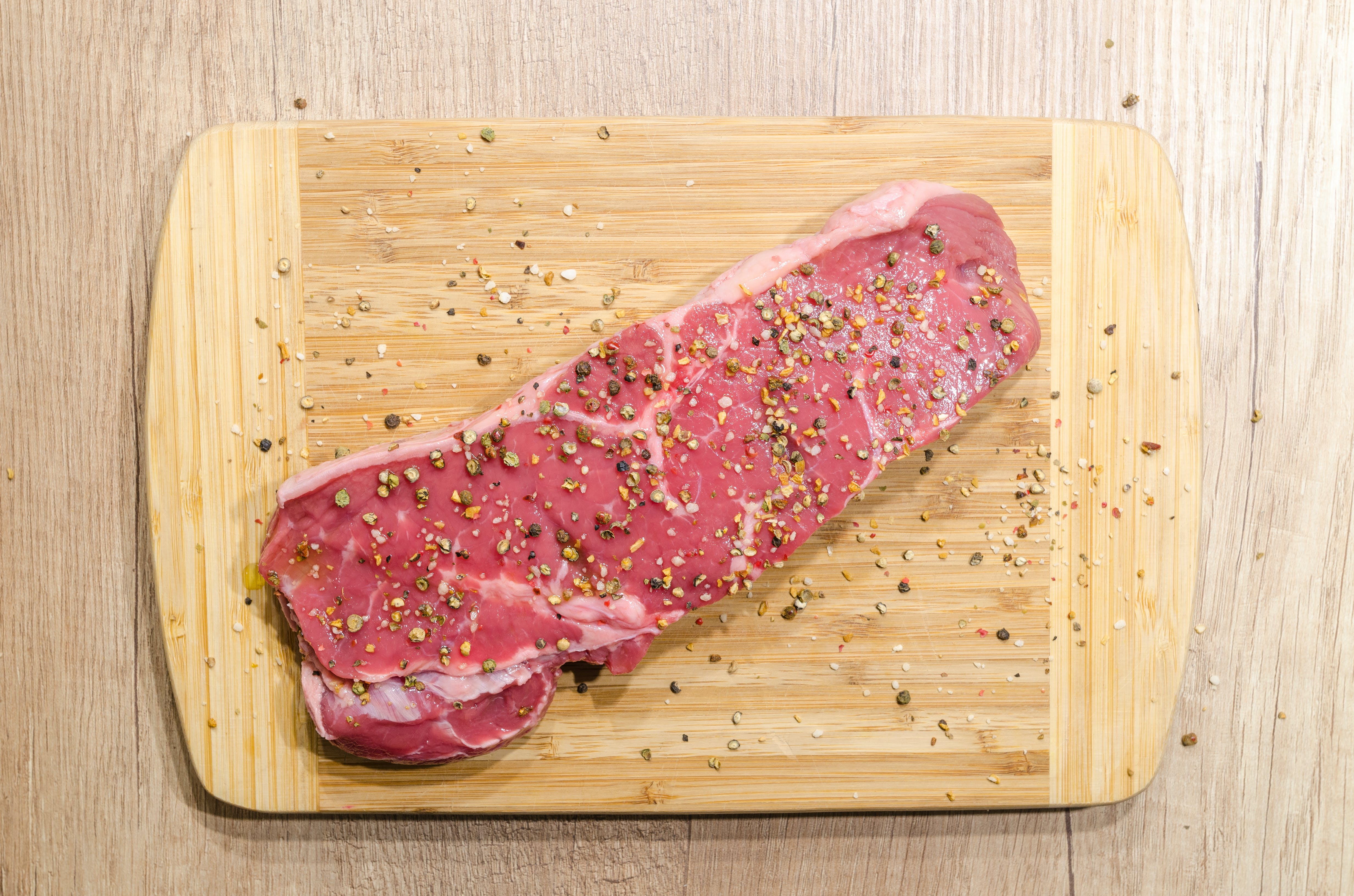 Flat Lay Photography of Slice of Meat on Top of Chopping Board Sprinkled With Ground Peppercorns