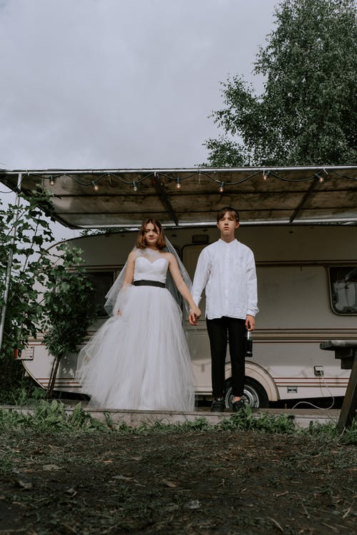Woman in White Wedding Gown Standing Beside Man in White Dress Shirt